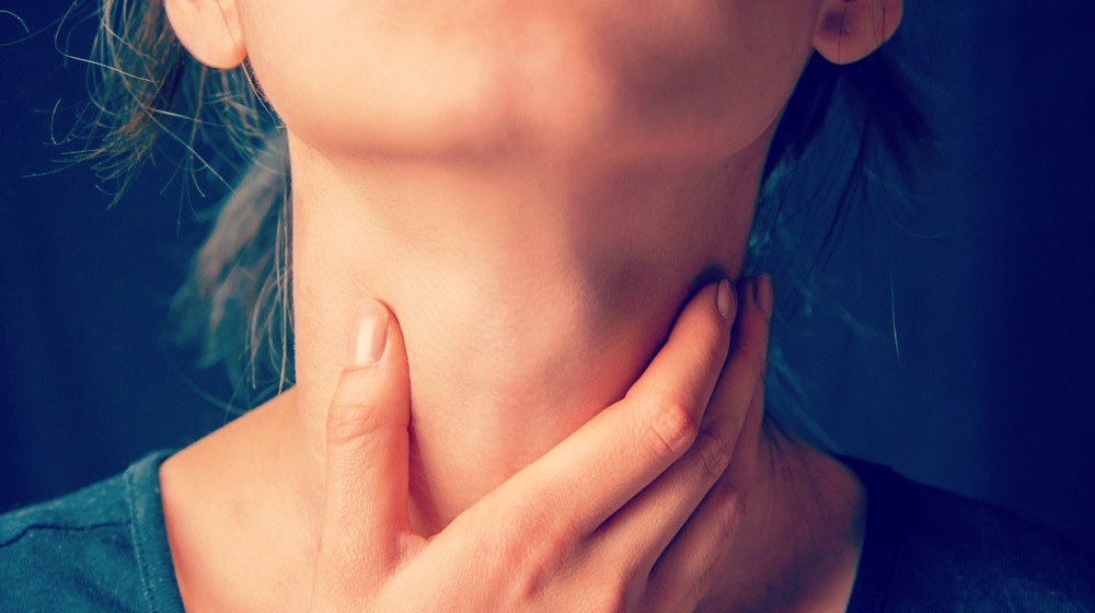 unrecognizable-woman-holds-her-throat-sore-throat-problems-ss-FEATURE-